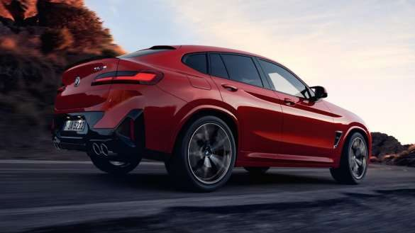 BMW X4 M F98 LCI Facelift 2021 M xDrive Dreiviertel-Heckansicht auf der Straße fahrend