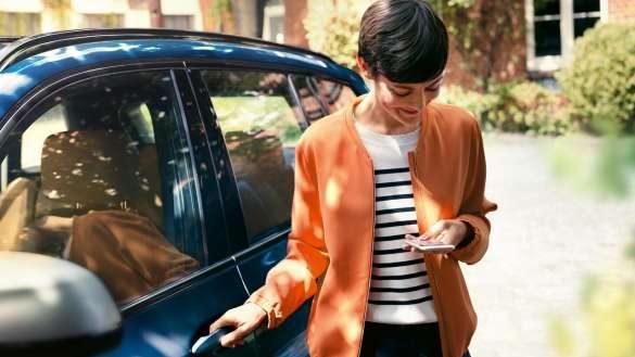 BMW Teleservices Frau guckt auf ihr Smartphone und öffnet Tür ihres BMW
